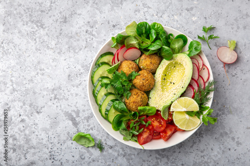 healthy vegan lunch bowl salad with avocado, falafel,cucumber, tomato and redish - 258979653