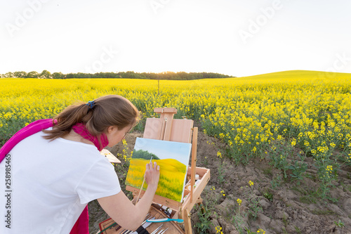 girl painter with an easel in a yellow rapeseed field