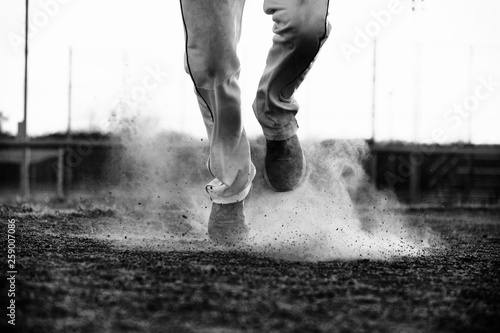 fototapeta na ścianę Black and white baseball concept with player running on dirt field close up.