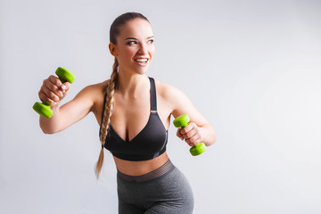 Beautiful young woman doing exercises with dumbbells. Photo athletic woman with perfect body on white background. Strength and motivation © galina_kovalenko