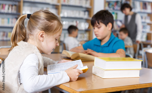 Preteen girl absorbedly reading book © JackF