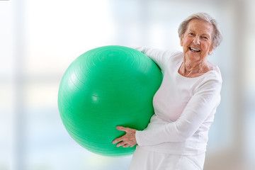 Senior Woman with fitness ball in gym.