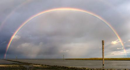 Ein eindrucksvoller Regenbogen über dem Wattenmeer von Bensersiel mit Wangerooge am Horizont