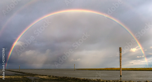 Ein eindrucksvoller Regenbogen über dem Wattenmeer von Bensersiel mit Wangerooge am Horizont © Werner