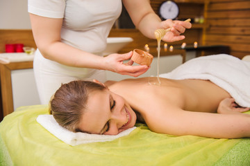 Young woman enjoying spa treatment with honey