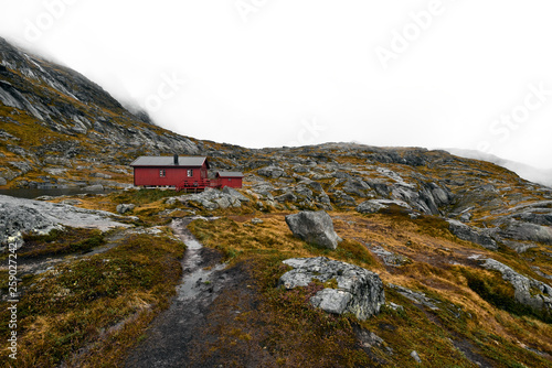 Hiking trail leading to a remote red wooden cabin in the mountains on the Lofoten in Norway