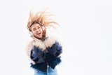 Happy carefree young woman dancing and listening to loud music in headphones over white background. Girl having fun emotions and laughing. Her hair waving. Copy space for text on right side