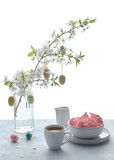 Springtime coffee and sweets on a wooden table with tree twig covered with blossoms and decorated with Easter Eggs