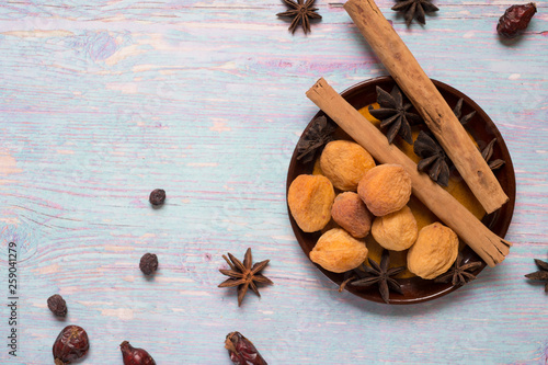 blue wooden background with cinnamon, anise, dog rose  and dried apricots © anakondasp