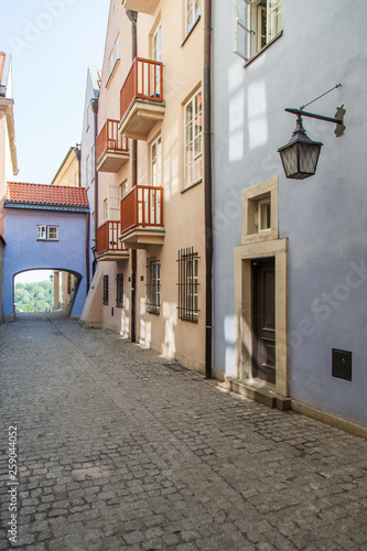 Narrow street with an arch and old lanterns. Warsaw.