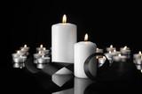Burning candles and mourning ribbon on black background