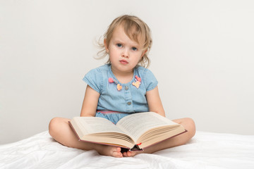 Cute little child in blue dress reading a book