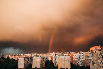 Dark rainy clouds. Stormy weather. Rainbow over the city. Beautiful landscape. Nature concept. Apocalyptic sky. The end of the world.