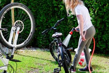 blondes mädchen beim fahrrad waschen