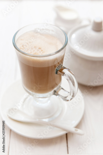 Raf coffee in transparent glass on a light wooden background. Delicious Russian most popular drinks.