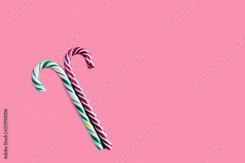two candy canes with a striped on a pink background - 259114006