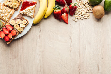 top view of bananas, strawberries, peanuts and toasts on wooden table with copy space