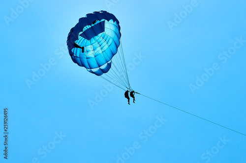 Parasailing flying against the background of the blue sky.  The concept of summer holidays, vacation. © Yerbolat