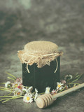 Honey in jar and daisies