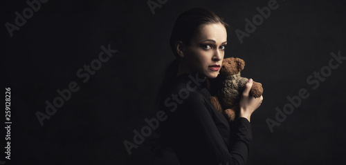 canvas print picture sad woman holds a teddy bear toy