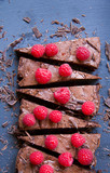 close up of slices of chocolate cake decorated with raspberries