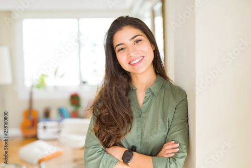 Leinwanddruck Bild Beautiful brunette woman smiling cheerful, looking happy and positive with crossed arms