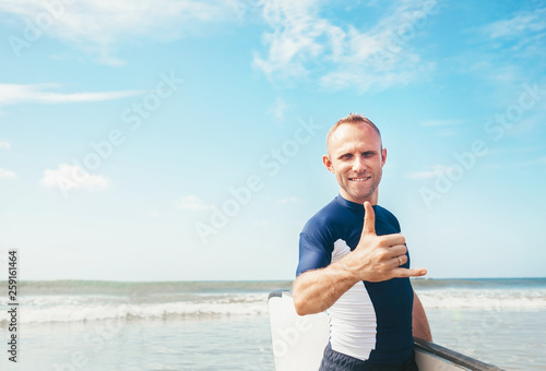 Leinwandbild Motiv Young man Surfer portrait showing surfer's famous Shaka sign gesture in camera when he comming with long surf board to waves. Active holidays spending concept.