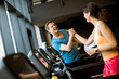 Close up of woman with trainer working out on treadmill in gym