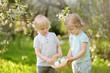 Leinwandbild Motiv Charming little children hunts for painted eggs in spring park on Easter day.