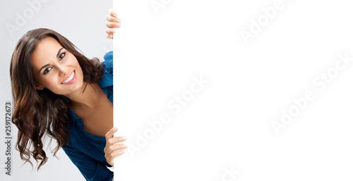 Leinwandbild Motiv Beautiful young woman showing blank signboard