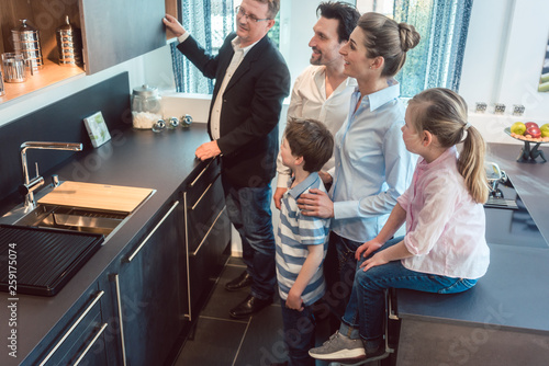Leinwandbild Motiv Family with kids looking at a kitchen in showroom