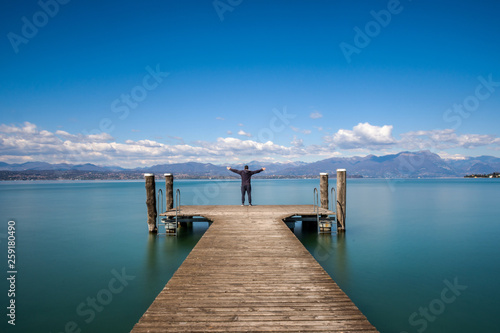 Acrylglas Pier Man standing on a jetty by tranquil lake