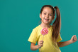 Beautiful cute little child girl with sweet candy lollipop isolated on blue background