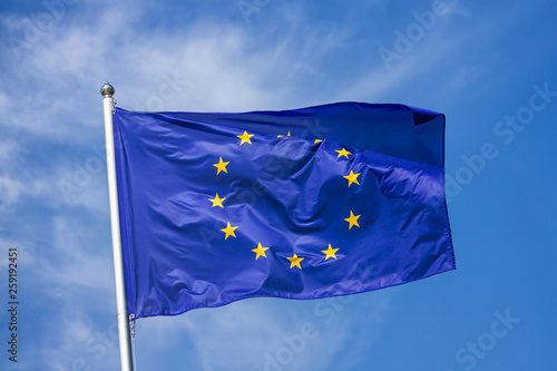 Leinwandbild Motiv Flag of the European Union waving in the wind on flagpole against the sky with clouds on sunny day, close-up