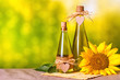 canvas print picture - Rural still-life - sunflower oil in bottles with flowers of sunflower (Helianthus annuus), closeup