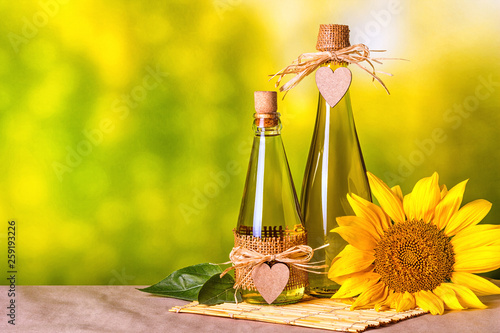 canvas print picture Rural still-life - sunflower oil in bottles with flowers of sunflower (Helianthus annuus), closeup