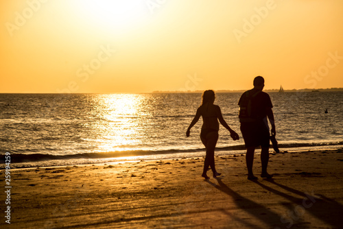 Silhouettes of people on an orange beach at sunset.
