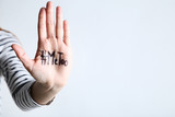 Woman showing palm with text Me Too on grey background
