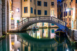 Canal in Venice at night with moored gondolas, Italy