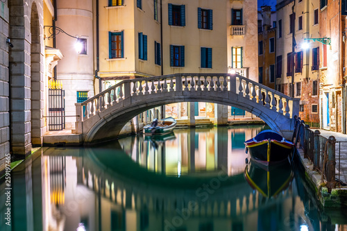 Canal in Venice at night with moored gondolas, Italy © Stefanos Kyriazis