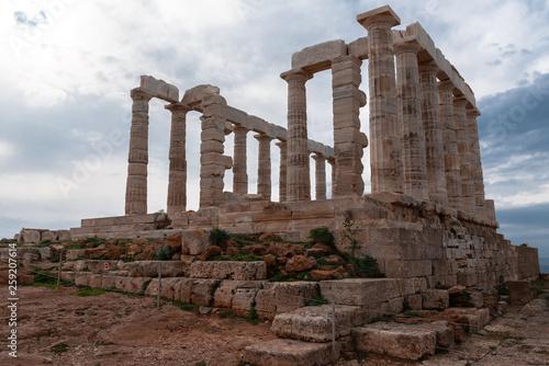 Greek temple ancient stones orange clouds blue sky