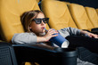 adorable child in 3d glasses sitting in cinema and drinking from paper cup