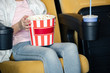 cropped view of child holding stripped paper cup with popcorn
