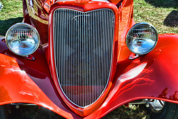 The vibrant grill and headlights of an old car.