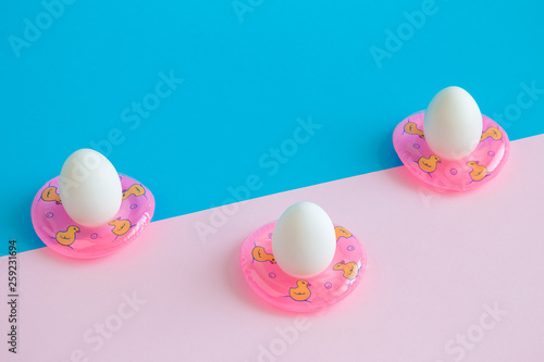 Three eggs in swimming pool floats abstract on colorful background.