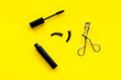 decorative cosmetic set with lash curler and mascara on yellow woman desk background top view