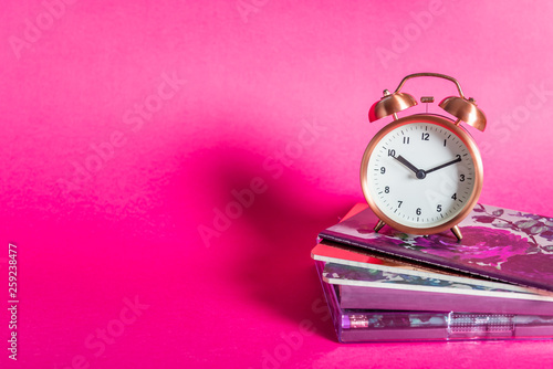 Different Notebooks and alarm clock on bright pink background - 259238477