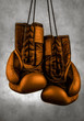 gold boxing gloves hanging on the wall, close-up.