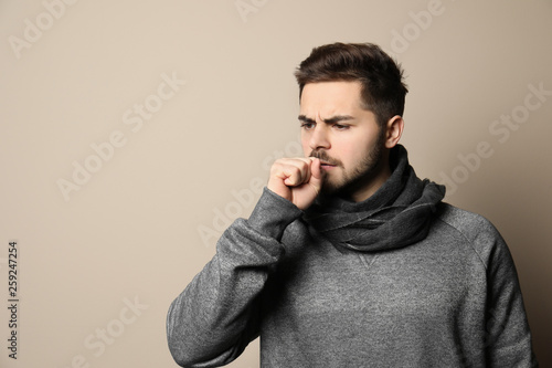 Leinwandbild Motiv Handsome young man coughing against color background. Space for text