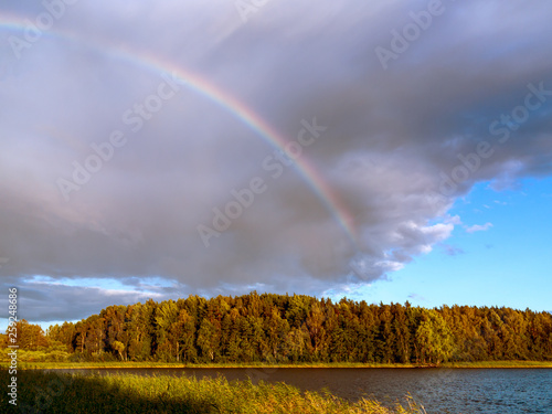 Rainbow over the lake and forest at sunset on a summer day © Галина Сандалова